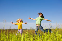 Happy woman and girl making exercises on field Stock Images