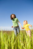 Happy woman and girl making exercises on field Stock Photography