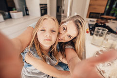 Happy woman and girl taking a selfie in kitchen Royalty Free Stock Image