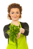 Happy woman gives parsley and dill Royalty Free Stock Image