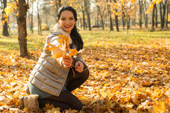 Happy woman giving autumn leaves Stock Photography
