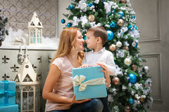 Happy woman giving Christmas present to her son. Young mother giving Christmas present to her son Stock Photography