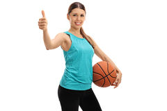 Happy woman giving a thumb up and holding a basketball Royalty Free Stock Photo