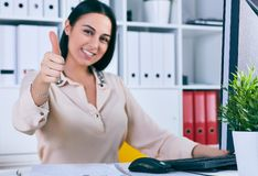 Happy woman giving thumbs up success sign sitting at computer PC with smiling face. Smiling businesswoman looks in camera sitting at workplace. White collar Stock Photos