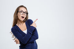 Happy woman in glasses pointing finger away Stock Images