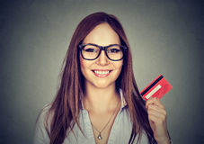 Happy woman in glasses showing credit card Stock Images