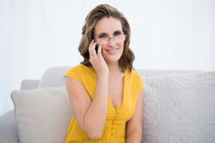 Happy woman with glasses talking on the phone sitting on sofa Royalty Free Stock Image