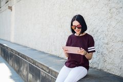 Happy woman in glasses using tablet pc in the street royalty free stock photography