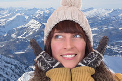 Happy woman with gloves and cap in the mountains Royalty Free Stock Photos
