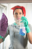 Happy woman in gloves cleaning window with rag and cleanser spray. At home Stock Photos