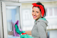 Happy woman in gloves cleaning window with rag and cleanser spray Royalty Free Stock Images