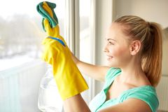 Happy woman in gloves cleaning window with rag Royalty Free Stock Images