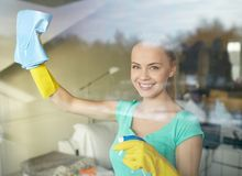Happy woman in gloves cleaning window with rag. People, housework and housekeeping concept - happy woman in gloves cleaning window with rag and cleanser spray at royalty free stock image