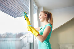Happy woman in gloves cleaning window with rag Royalty Free Stock Photos