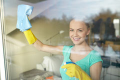 Happy woman in gloves cleaning window with rag Stock Photos