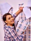 Happy woman glues wallpaper . Royalty Free Stock Image