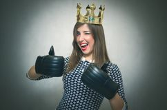 Happy woman. Winner of beauty contest. Bossy girl. Happy woman with gold crown on her head and in a boxing gloves showing a thumb up. Women`s Match. Women`s Royalty Free Stock Photography