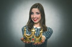 Happy woman with golden crown. First place concept. Happy woman is stretching ahead a gold crown isolated on gray background. Award ceremony. Transfer of power Royalty Free Stock Image
