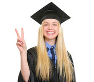 Happy woman in graduation gown showing victory Royalty Free Stock Photo