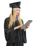 Happy woman in graduation gown using tablet pc Royalty Free Stock Images
