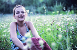 Happy woman in grass. Happy young woman casually sitting in an overgrown field of wildflowers, in a clearing near a wooded area Stock Photo