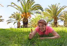 Happy woman on a grass in orchard with palm trees Royalty Free Stock Image