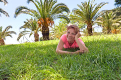 Happy woman on a grass in orchard with palm trees Stock Photography
