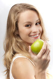 Happy woman with green apple. Portrait of happy young blond woman with green apple; isolated on white background royalty free stock photo