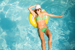 Happy woman in green bikini floating on inflatable tube in swimming pool Royalty Free Stock Photos
