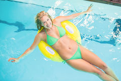 Happy woman in green bikini relaxing on inflatable tube in swimming pool Royalty Free Stock Photo