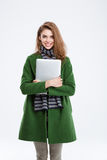 Happy woman in green coat holding laptop. Portrait of a happy woman in green coat holding laptop and looking at camera isolated on a white background royalty free stock images