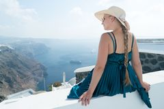 Happy woman in green dress and sun hat enjoying her holidays on Santorini, Greece. View on Caldera and Aegean sea from. Imerovigli. Active, travel, tourist royalty free stock images