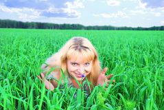 Happy woman in green field. Happy young blond woman lying in green field or meadow smelling flowers Stock Images