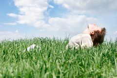Happy woman in green grass stock image