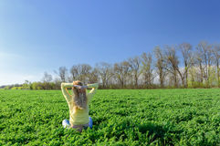 Happy woman on the green grass in the meadow Royalty Free Stock Photography