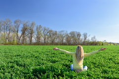 Happy woman on the green grass in the meadow Royalty Free Stock Photo
