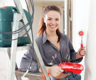 Happy  woman paints wall with roller Stock Photos