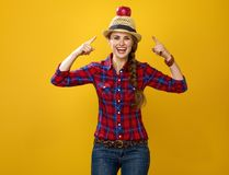 Happy woman grower isolated on yellow pointing on apple on head Royalty Free Stock Photos
