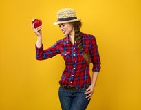 Happy woman grower isolated on yellow posing with an apple. Healthy food to your table. Portrait of happy modern woman grower in checkered shirt isolated on Royalty Free Stock Photography