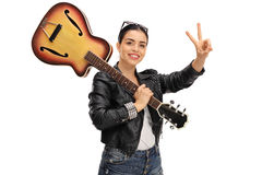 Happy woman with a guitar making a peace sign Stock Photography