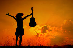 Happy Woman and guitar with sunset silhouette Royalty Free Stock Image