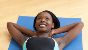 Happy woman in gym outfit excercising Stock Photography