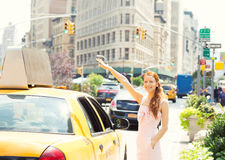 Happy woman hailing taxi cab in Manhattan  New York city. Attractive smiling woman in New York City. Beautiful happy summer shopper hailing for taxi cab outside Royalty Free Stock Photography