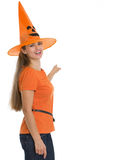 Happy woman in Halloween hat pointing on back Stock Photo