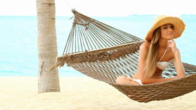 Happy woman on hammock at the exotic beach stock video