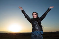 Happy woman with hand in the air celebrating  in the dawn Royalty Free Stock Photography