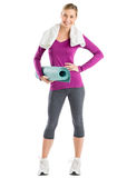 Happy Woman With Hand On Hip While Holding Exercise Mat Stock Image