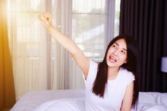 Happy woman with hand raised on bed in bedroom Royalty Free Stock Image