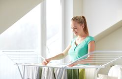 Happy woman hanging clothes on dryer at home Royalty Free Stock Image