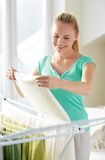 Happy woman hanging clothes on dryer at home Royalty Free Stock Photography
